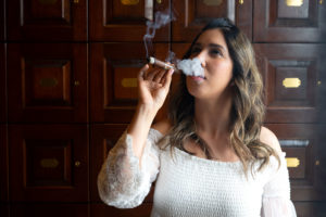 woman puffing cigar smoke